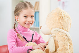 child using a stethoscope on bear